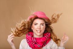 有卷发的女孩在桃红色帽子和围巾 图库摄影