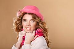 有卷发的女孩在桃红色帽子和围巾 库存图片