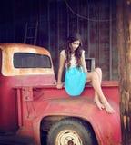 有卷发的女孩在老葡萄酒卡车 免版税库存照片