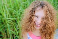 有卷发的小美丽的女孩 免版税库存图片