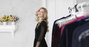 有卷发的年轻白肤金发的妇女在选择新的内衣的黑便服Â早晨 影视素材