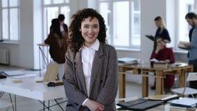 有卷发的微笑对照相机的愉快的正面年轻白种人女商人中景画象在现代办公室 股票录像