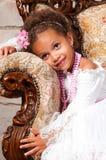 有卷发的微笑的非洲女孩在一根白色鞋带在葡萄酒椅子穿戴 图库摄影
