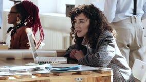 有卷发的愉快的年轻微笑的欧洲女商人谈话与坐在时髦现代办公室桌上的同事 股票视频