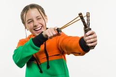 有卷发的淘气女孩少年拿着一个弹弓 空白 免版税库存图片