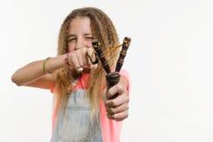 有卷发的淘气女孩少年拿着一个弹弓 免版税库存图片