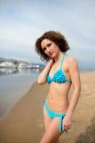 有卷发的美丽的女孩在海滩的蓝色比基尼泳装 库存图片
