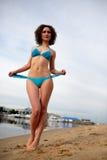 有卷发的美丽的女孩在红色比基尼泳装坐海滩 免版税图库摄影