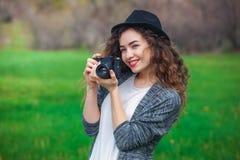 有卷发的美丽的女孩摄影师拿着一台照相机并且做照片,春天户外在公园 免版税库存照片