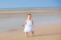 有卷发的美丽的女婴在热带海滩 免版税图库摄影