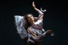 有卷发的美丽的深色的在性感的银色缎飞行的女孩在黑暗中和光穿戴在舞蹈的令人敬畏的姿势 免版税库存图片