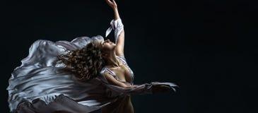 有卷发的美丽的深色的在性感的银色缎飞行的女孩在黑暗中和光穿戴在舞蹈的令人敬畏的姿势 免版税库存照片
