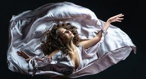有卷发的美丽的深色的在性感的银色缎飞行的女孩在黑暗中和光穿戴在舞蹈的令人敬畏的姿势 免版税图库摄影
