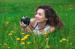 有卷发的美丽,可爱的女孩摄影师举行一台照相机和说谎在草用开花的蒲公英 免版税库存图片