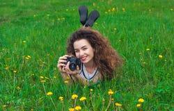 有卷发的美丽,可爱的女孩摄影师举行一台照相机和说谎在草用开花的蒲公英 库存图片