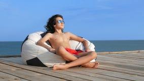 有卷发的英俊的少年男孩在太阳镜在袋子椅子坐在海的一个木大阳台 ??  影视素材