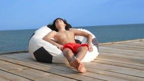 有卷发的英俊的少年男孩在太阳镜在袋子椅子坐在海的一个木大阳台 ??  股票录像