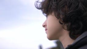 有卷发的逗人喜爱的少年反对天空蔚蓝4k,慢动作射击 股票录像