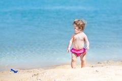 有卷发的逗人喜爱的滑稽的女婴在海滩的沙子 免版税图库摄影
