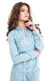 有卷发的Thoughful可爱的少妇在牛仔裤衬衣 免版税库存图片