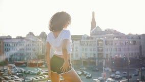 有卷发跳舞的可爱的混血儿年轻女人在现代大厦背景-日落 股票视频