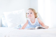 有卷发阅读书的美丽的矮小的小孩女孩 免版税库存照片