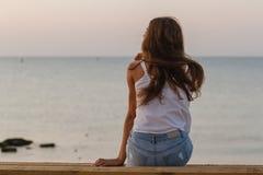 有卷发sittin的少妇在早晨海滩 图库摄影