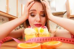 有卷尺和蛋糕的妇女 饮食困境 免版税库存图片