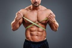 有卷尺的爱好健美者测量的腰部 免版税库存照片