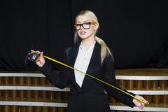 有卷尺的美丽的白肤金发的女实业家在橙色玻璃和黑衣服的顶楼办公室 到达天空的企业概念金黄回归键所有权 免版税图库摄影