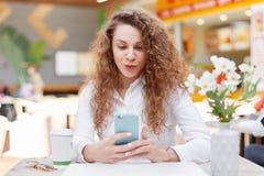 有卷曲分蘖性头发的正面美丽的女性拿着手机现代手机的surfes互联网或做selfie,坐agains 图库摄影