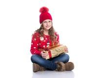 有卷曲发型佩带的红色的迷人的微笑的小女孩在白色编织了拿着圣诞节礼物的毛线衣和帽子被隔绝 库存图片