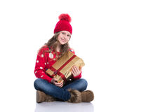 有卷曲发型佩带的红色的迷人的微笑的小女孩在白色编织了拿着圣诞节礼物的毛线衣和帽子被隔绝 免版税图库摄影