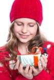 有卷曲发型佩带的红色的迷人的微笑的小女孩在白色编织了拿着圣诞节礼物的毛线衣和帽子被隔绝 免版税库存照片