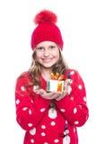 有卷曲发型佩带的红色的迷人的微笑的小女孩在白色编织了拿着圣诞节礼物的毛线衣和帽子被隔绝 免版税库存图片