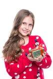 有卷曲发型佩带的红色的迷人的微笑的小女孩在白色编织了毛线衣和拿着圣诞节礼物被隔绝 库存照片