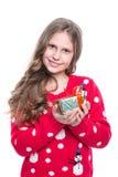 有卷曲发型佩带的红色的迷人的微笑的小女孩在白色编织了毛线衣和拿着圣诞节礼物被隔绝 免版税库存照片