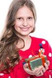 有卷曲发型佩带的红色的迷人的微笑的小女孩在白色编织了毛线衣和拿着圣诞节礼物被隔绝 免版税图库摄影