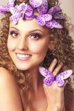 有卷曲发型和蓝色蝴蝶的可爱的少妇 免版税库存照片