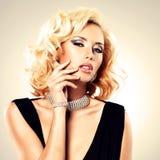 有卷曲发型和银手镯的美丽的妇女 图库摄影