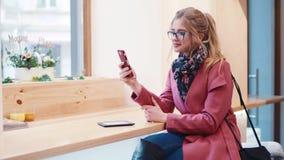 有卷曲发型的愉快地微笑时髦的年轻欧洲的女孩,当使用她的手机为发短信给消息时 影视素材