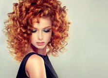 有卷曲发型的红发女孩 免版税图库摄影