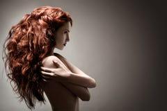 有卷曲发型的美丽的妇女在灰色背景 免版税库存照片