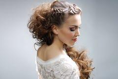 有卷曲发型的美丽的妇女 免版税库存图片