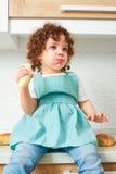 有卷曲女儿的妈妈在到位准备的厨房里 B 免版税库存图片