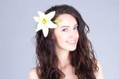 有卷曲棕色头发和一朵花的俏丽的妇女在她的头发微笑与牙的 免版税库存照片