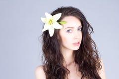 有卷曲棕色头发和一朵花的妇女在她的头发 库存照片