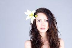 有卷曲棕色头发和一朵花的妇女在她的头发 库存图片