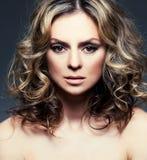 有卷曲棕色头发的美丽的中间妇女 图库摄影