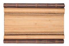 有卷曲的边缘和绳索的竹席子,隔绝在白色背景 库存照片